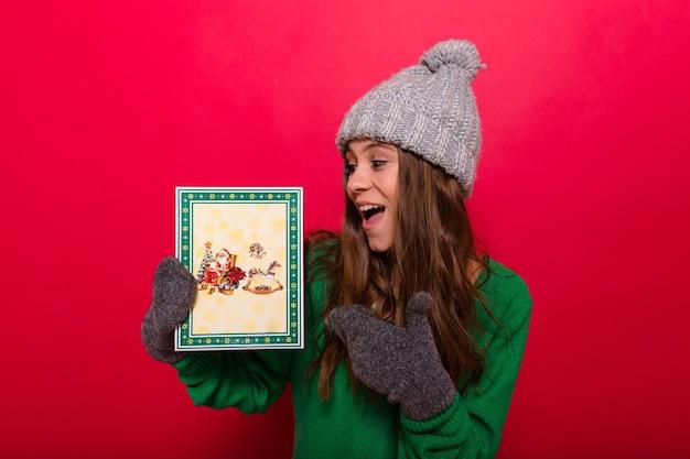 Femme posant avec un chapeau d'hiver et des gants tenant un cadeau de noël