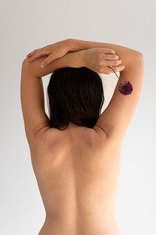 Femme posant avec confiance dans le nu et montrant en arrière