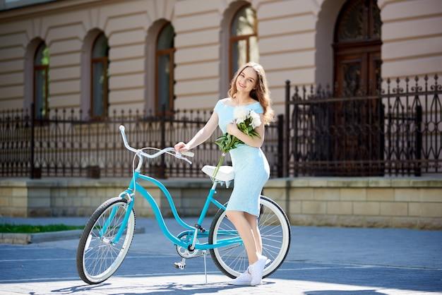 Femme posant à côté de la bicyclette devant le bâtiment historique