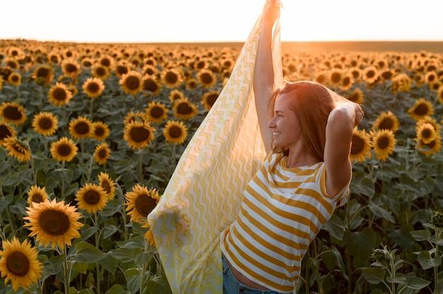Femme posant dans un champ de tournesol au coucher du soleil