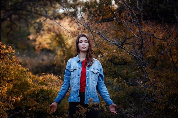Femme posant dans la forêt des montagnes. une femme dans une veste en jean. montagnes en automne