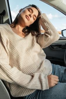 Femme posant dans sa voiture lors d'un road trip