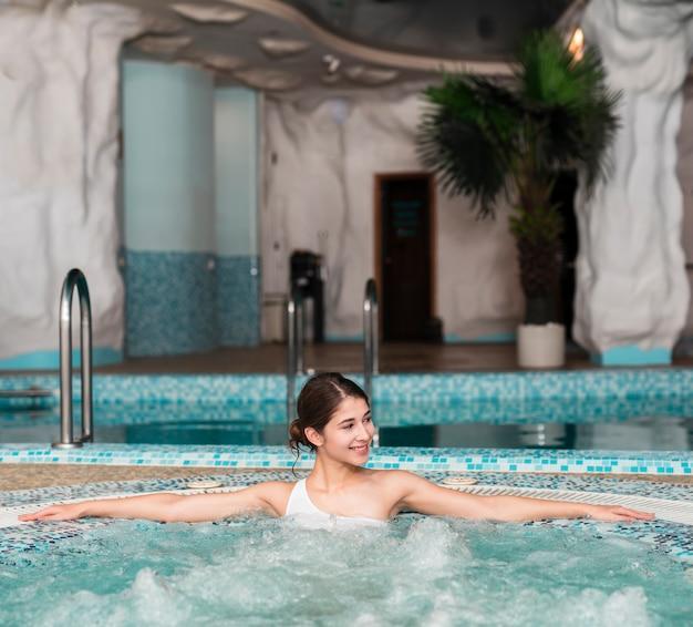 Femme posant détendue dans le bain à remous