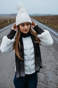 Femme posant à l'extérieur sur la route