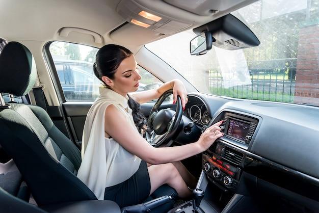 Femme posant à l'intérieur de la voiture assis dans le siège du conducteur
