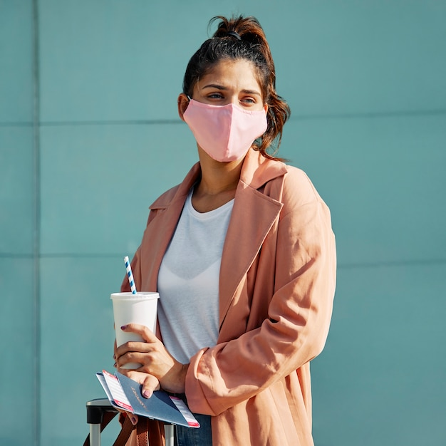 Femme posant avec masque médical et passeport à l'aéroport pendant la pandémie