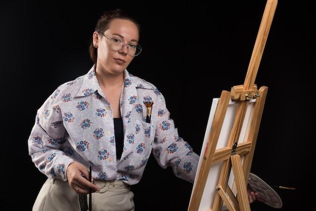 Femme posant avec des pinceaux et toile sur fond noir. photo de haute qualité