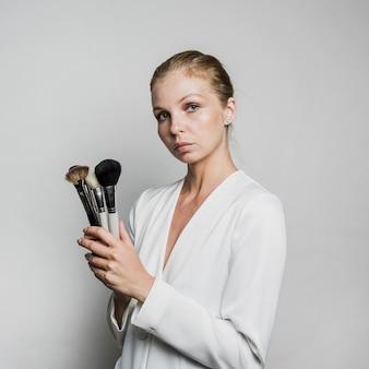 Femme posant avec des pinceaux
