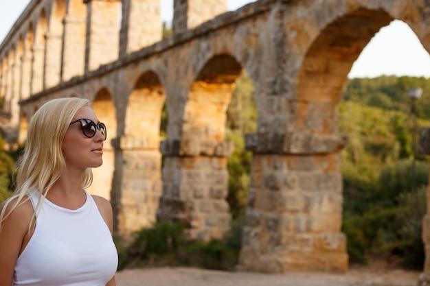 Femme posant près de l'aqueduc romain pont del diable à tarragone au coucher du soleil
