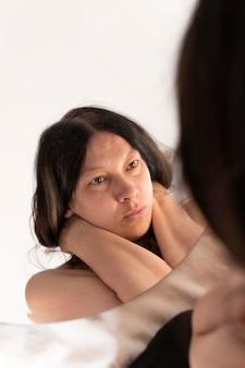 Femme posant en se regardant sensuellement dans le miroir