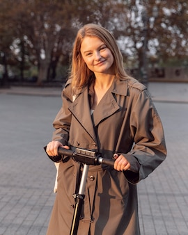 Femme posant avec son scooter électrique dans la ville