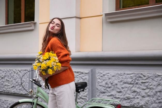 Femme posant avec son vélo tout en faisant la moue des lèvres et tenant des fleurs