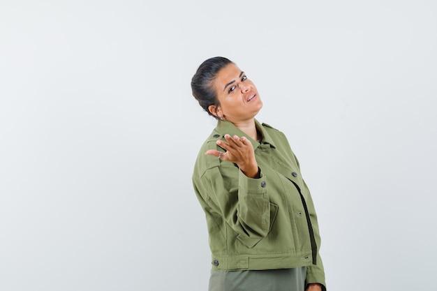 Femme posant tout en étirant la main en veste, t-shirt et à la recherche sensible.