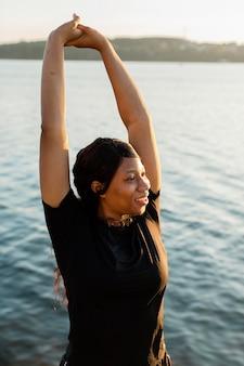 Femme posant tout en s'étirant au bord du lac