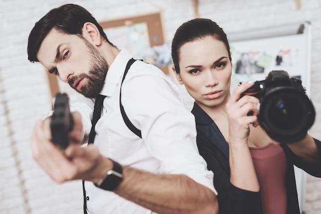 Une femme pose avec une caméra, un homme pose avec une arme à feu.