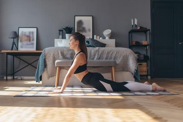Femme en pose de cobra, elle exerce sur le sol les bras étendus et le haut du corps relevé vers le haut en hyperextendu.