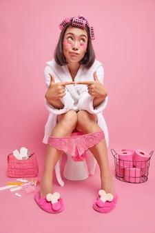 Femme pose sur la cuvette des toilettes étant plongé dans ses pensées porte un peignoir blanc confortable applique des rouleaux de cheveux des patchs de beauté pose aux toilettes isolé sur rose