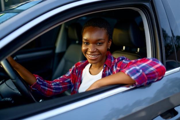 Une femme pose dans une voiture brillante, une station de lavage automatique des mains. industrie ou entreprise de lavage de voitures. la personne de sexe féminin nettoie son véhicule de la saleté à l'extérieur