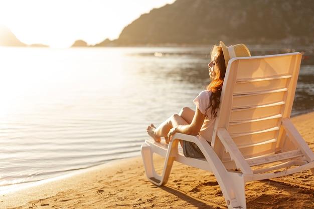 Femme, pose, salon, regarder mer