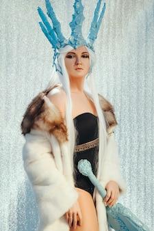 Femme pose tout en portant le costume de reine des glaces