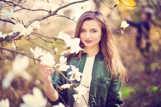 Femme, poser, magnolia, jardin