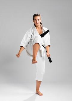 Femme en position de combat portant l'uniforme blanc sur fond gris