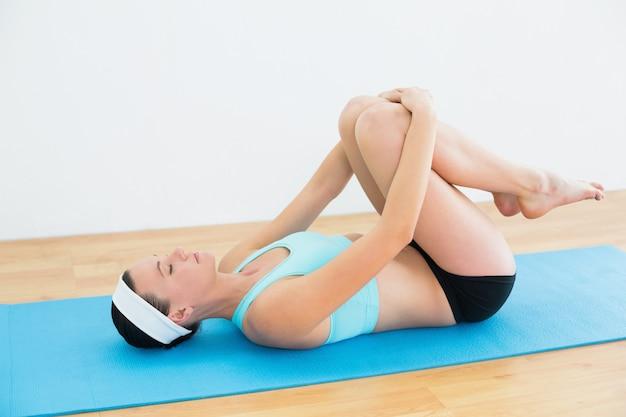 Femme en position couchée en position couchée sur un tapis de yoga