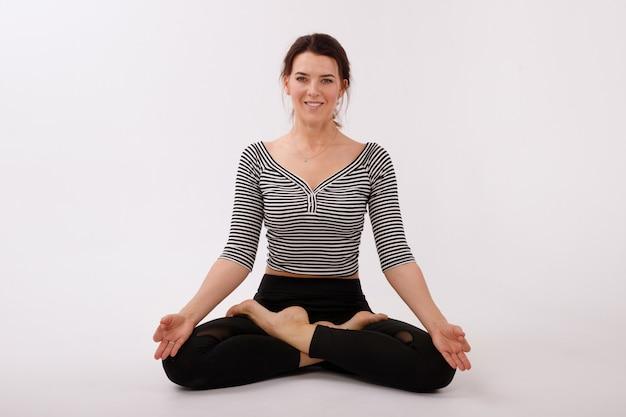 Femme en position du lotus sur fond blanc isolé. legging et haut de sport noirs. journée internationale du yoga
