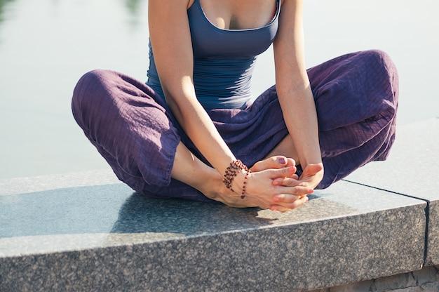 Femme en position de yoga lotus en plein air