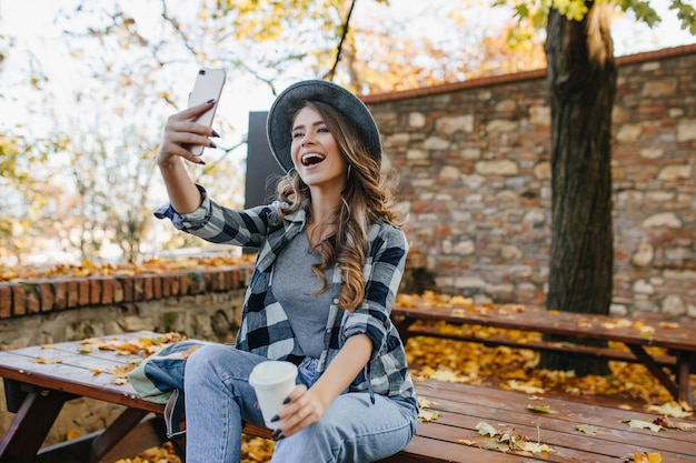 Femme positive aux cheveux brun clair faisant selfie tout en buvant du café dans le parc de l'automne