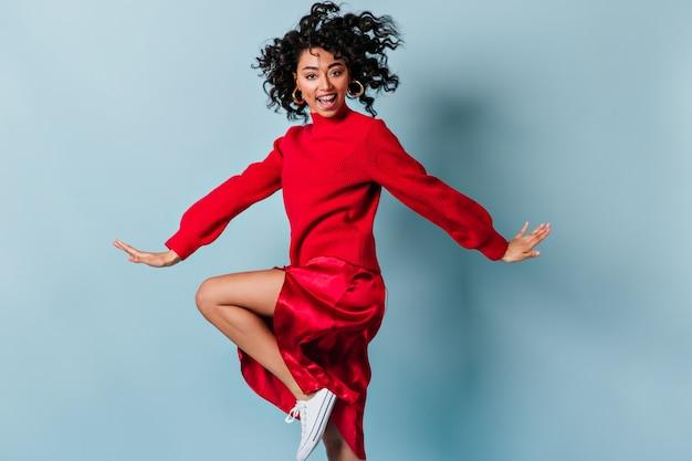 Femme positive aux cheveux ondulés dansant sur le mur bleu