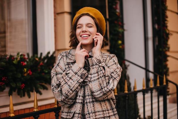 Femme positive en béret orange et manteau rit en parlant au téléphone contre le mur de la ville