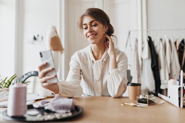 Une femme positive en blouse beige tient un téléphone et s'assoit au bureau