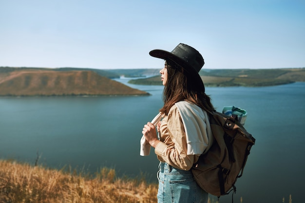 Femme positive en chapeau de cowboy marchant dans la région de bakota