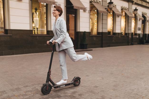 Femme positive en costume gris équitation scooter à l'extérieur. charmante fille aux cheveux courts en veste et pantalon souriant et se promenant dans la ville