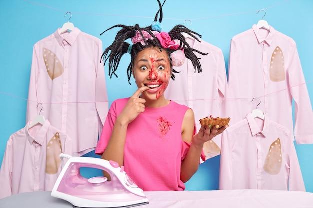 Une femme positive avec des dreadlocks aime manger une tarte savoureuse a le visage