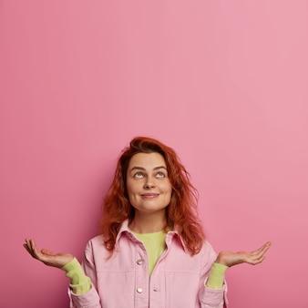 Une femme positive espère que les rêves deviennent réalité, se tient debout avec la paume levée et regarde au-dessus, fait une demande, a les cheveux roux, vêtue de vêtements élégants