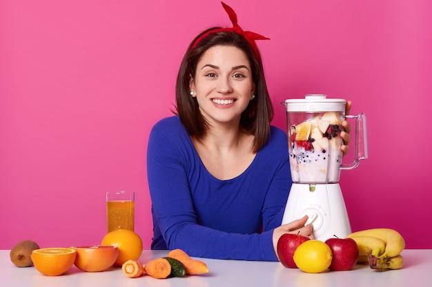 Une femme positive avec une expression faciale joyeuse, étant en pleine humeur, mélange les fruits dans un mélangeur pour faire un smoothie, vêtue d'un pull bleu et d'une bande de cheveux, aime boire du jus frais. concept de mode de vie.