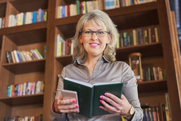 Femme positive avec journal d'affaires, fond d'étagère