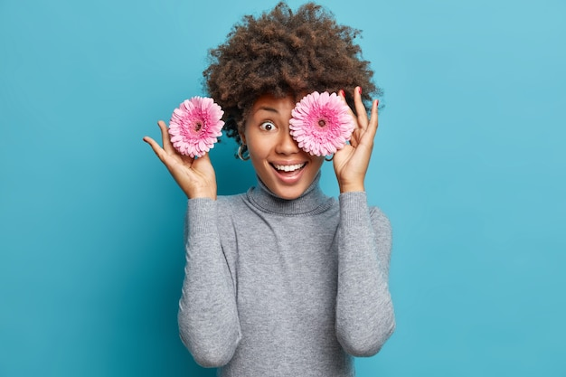 Femme positive ludique aux cheveux bouclés détient deux gerberas roses sur les yeux sourit largement porte col roulé gris occasionnel isolé sur mur bleu