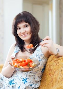 Femme positive mange salade végétarienne