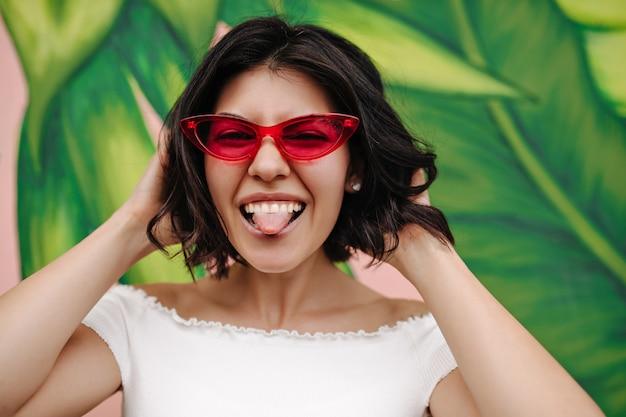 Femme positive montrant la langue devant le graffiti vert