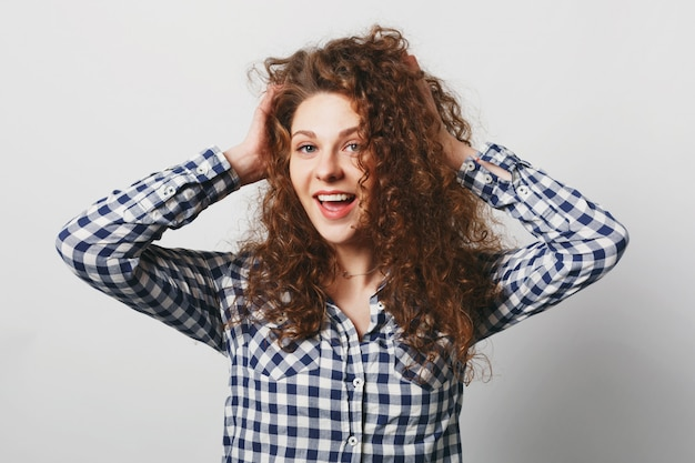 Femme positive montre ses cheveux bouclés touffus, porte une chemise à carreaux décontractée, isolé sur blanc