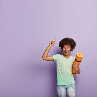 Femme positive à la peau foncée avec une coiffure afro, porte un t-shirt et des leggings décontractés, a une méditation de remise en forme