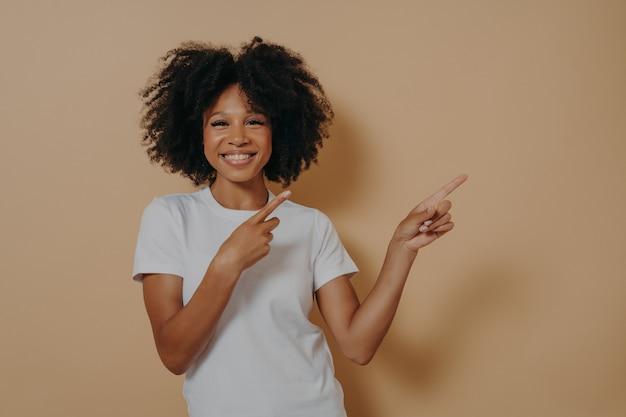 Femme positive à la peau foncée et joyeuse vêtue d'un t-shirt de base blanc pointant vers l'espace de copie isolé sur fond beige, affichage publicitaire du produit, montrant la place pour votre promotion publicitaire