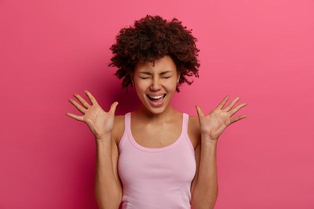 Une femme positive à la peau sombre rit et lève les paumes, se sent très heureuse, ne peut pas arrêter de rire, ferme les yeux et glousse, porte un gilet décontracté, isolé sur un mur rose. émotions et sentiments positifs