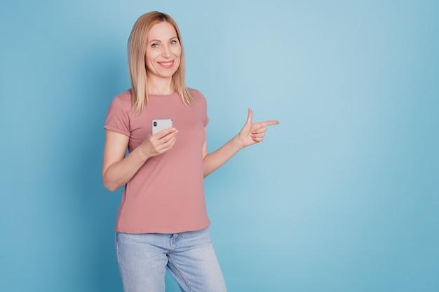 Femme positive point index copyspace utiliser téléphone portable présent publicités sur les réseaux sociaux promo manière directe fond de couleur bleu isolé