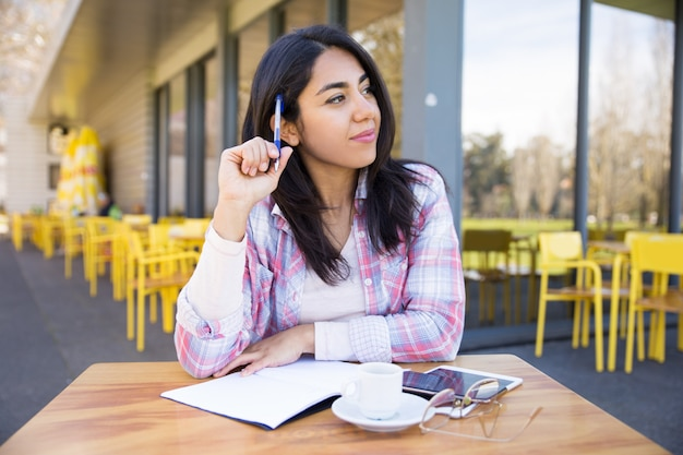 Femme positive, prendre des notes dans un café en plein air
