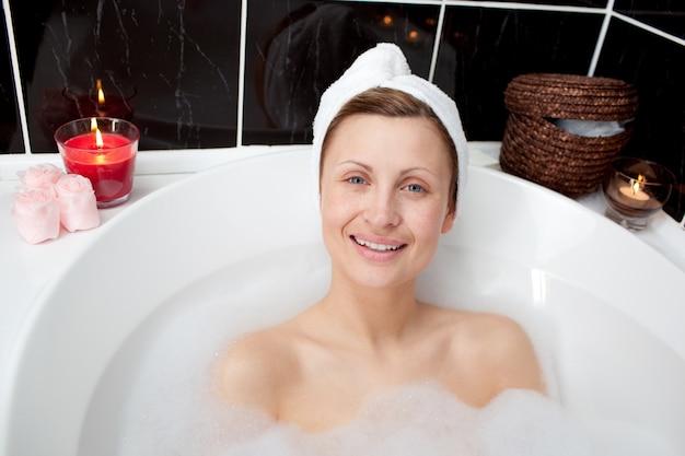 Femme positive relaxante dans un bain moussant