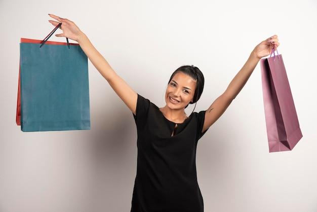 Femme positive avec des sacs à provisions posant sur un mur blanc.